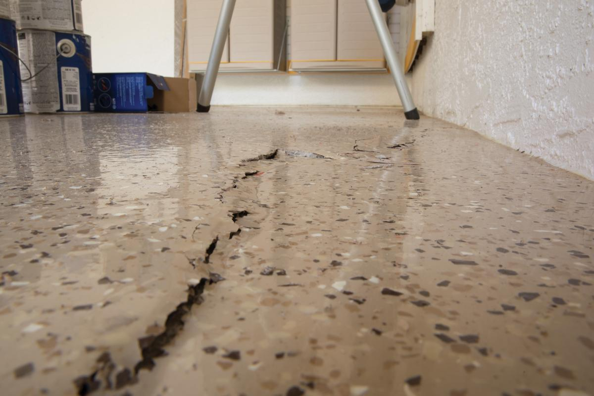 cracked, sunken concrete garage floor slab