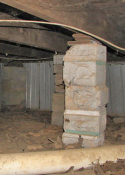 a sagging, rotting crawl space with concrete supports and wood shimmying