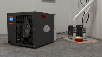 A sump pump and SaniDry dehumidifier in a basement
