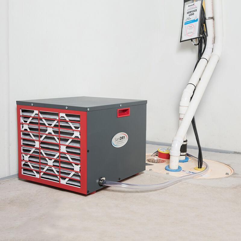 A SaniDry Sedona dehumidifier, TripleSafe Sump Pump and WaterGuard drainage system inside a concrete basement