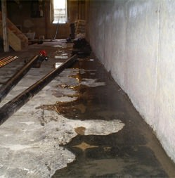 Basement with water on the concrete floor along the wall