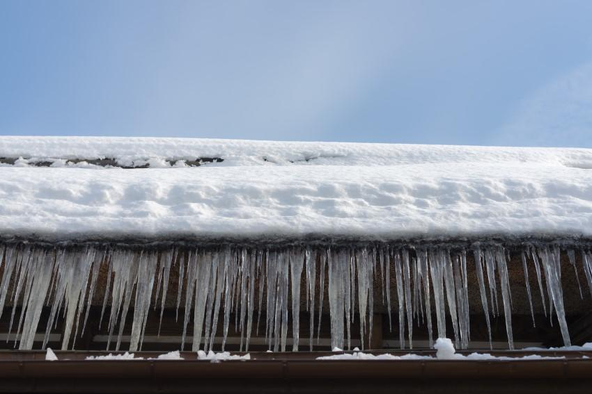 Icicles hang off the edge of a roof