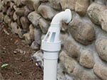 IceGuard device installed on a sump pump discharge line coming out of a stone foundation