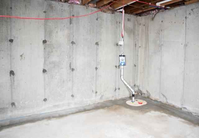 A sump pump and hidden drainage system inside a basement