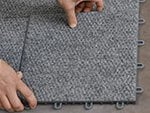 Closeup of ThermalDry® carpet tile installation in a basement