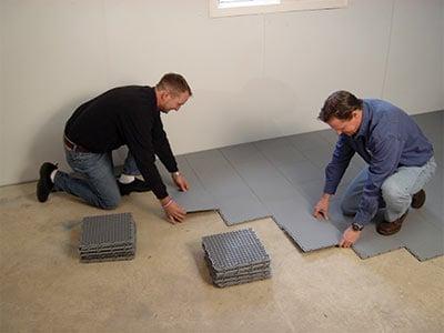Two contractors installing ThermalDry basement floor matting over a concrete floor
