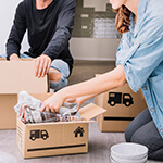 Two People Packing Boxes Together