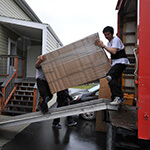 Professional Movers Lifting A Big Object Out Of A Moving Truck