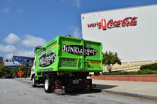 Junk lugger truck in front of large building