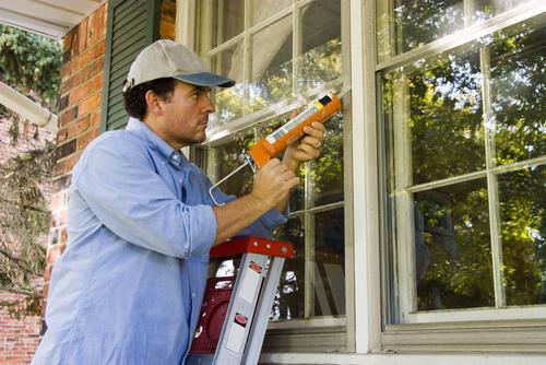 Contractor sealing around windows