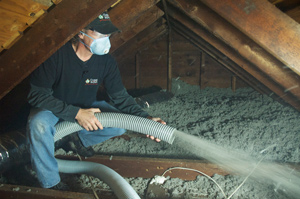 Contractor blowing attic insulation