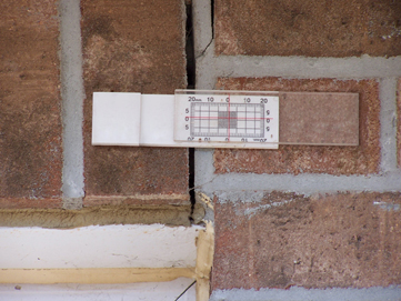 Measuring a crack in a brick foundation wall in Kahoka, Missouri