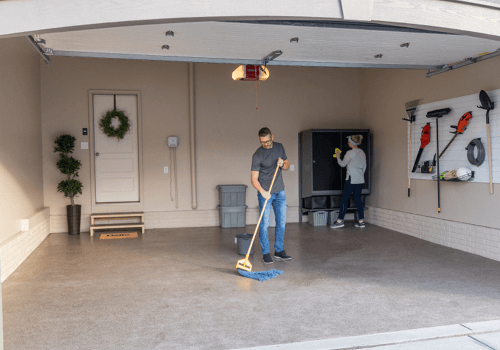People cleaning garage floor and cabinets