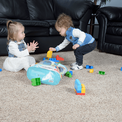 Young kids playing with toys in playroom.
