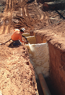 Crew installing PolyLevel<sup>®</sup> spray foam trench breakers