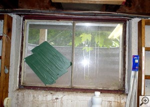 An old, rotting basement window set in a rusty steel frame with a patch over a broken spot.