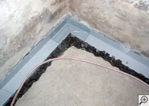 Installation in progress of a perimeter basement drain system
