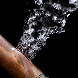 A bursting copper pipe, with water gushing out.