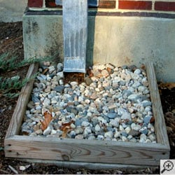 A home's gutter discharging directly into a gravel drywell.