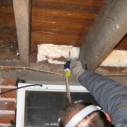 Closed cell spray foam insulation being installed in a basement