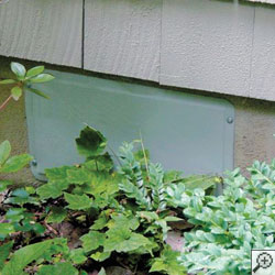 A crawl space vent cover installed on a crawl space opening.