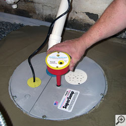 A sump pump installation being finished, with the sump alarm being set in place.