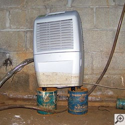 A basement dehumidifier sitting on top of two cans to keep it out of the water.