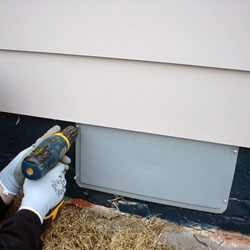 a contractor sealing a crawl space vent with a plastic, airtight cover
