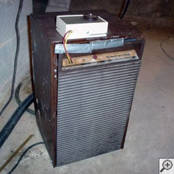 An old broken basement dehumidifier that's been cobbled back together with duct tape.