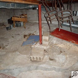 A basement with a dirt floor that is experiencing moisture issues.