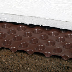 Crawl space drainage matting installed on a dirt floor