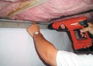 A crawl space contractor installing a waterproof vapor barrier system on the foundation walls
