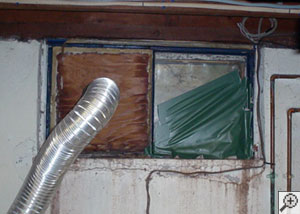A basement window system that's rotted and  has been damaged over time.