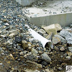 A foundation drainage system discharge line with no protective covering on the discharge opening.