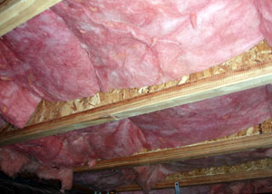 fiberglass batt insulation installed within the floor joists in a crawl space
