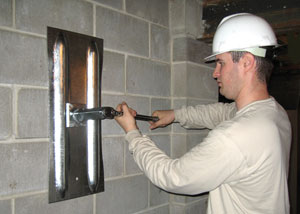 a foundation contractor installing a wall anchor system