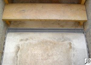 A grated basement drain system for leaking basement staircases.