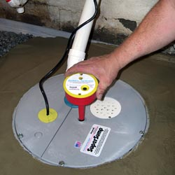 A contractor completing the installation of a sump pump system
