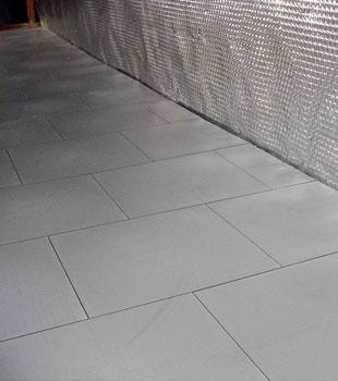 Basement subfloor tiles installed on a concrete slab floor.