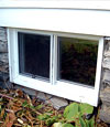 A vinyl basement window with energy efficient glass installed in a basement.