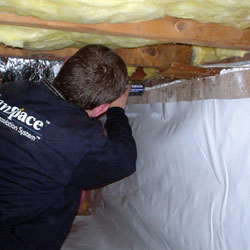 A contractor installing a crawl space vapor barrier on the foundation walls.