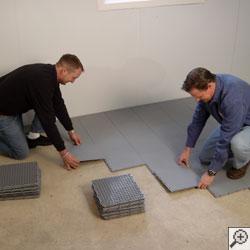 Two contractors installing ThermalDry® floor matting tiles on a basement floor.