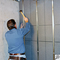 A contractor installing a basement wall insulation panel on a concrete wall.