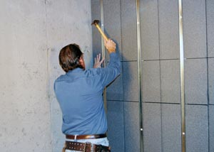 A contractor installing rigid foam insulation on a basement wall.