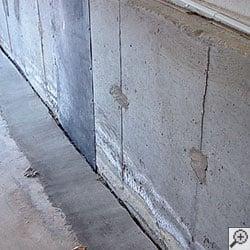 An open gap running along a concrete basement wall, as part of a basement waterproofing system.