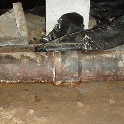 A rusty sewage pipe leaking in a crawl space