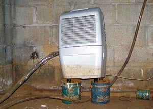 A dehumidifier that shows signs of being half-submerged in water in a crawl space in the past.