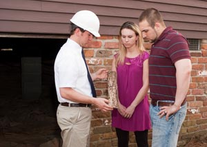 A pest inspector showing termite damaged wood to two homeowners.