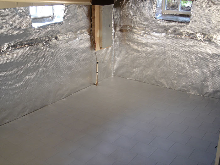 A basement with a radiant heat barrier and vapor barrier on the walls, and a vapor barrier and waterproof floor matting on the concrete slab floor.