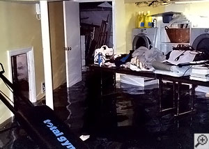 A flooded laundry room with over a foot of water.